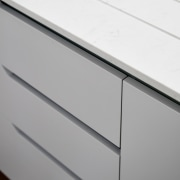White countertops compliment the grey cabinets angle, chest of drawers, drawer, furniture, line, product, product design, sideboard, gray, white