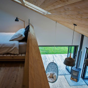 The bedroom is connected to the main living architecture, attic, daylighting, floor, furniture, home, house, interior design, roof, room, wood, brown, gray
