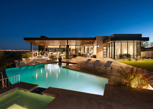 At night, this home lights up the desert architecture, backyard, estate, facade, home, house, lighting, mansion, property, real estate, residential area, resort, swimming pool, villa, blue