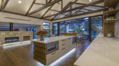 For this resort-style home, the central island in architecture, building, cabinetry, ceiling, countertop, daylighting, design, estate, floor, flooring, furniture, hardwood, home, house, interior design, kitchen, lighting, living room, loft, property, real estate, room, window, wood, wood flooring, brown, gray
