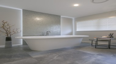 As well as a buoyant bather, this bathroom's architecture, bathroom, bathtub, beige, building, ceiling, ceramic, estate, floor, flooring, furniture, home, house, interior design, limestone, material property, plumbing fixture, property, real estate, room, tap, tile, wall, gray