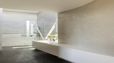 This understated ensuite features a sculptural vanity that