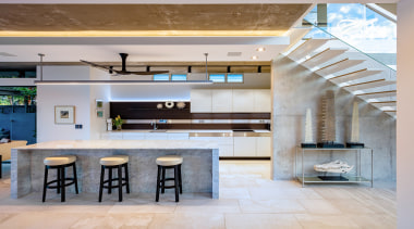 ​​​​​​​Read the full story. architecture, bar stool, building, cabinetry, ceiling, countertop, design, floor, flooring, furniture, home, house, interior design, kitchen, lighting, living room, lobby, loft, material property, property, real estate, room, table, tile, wall, gray