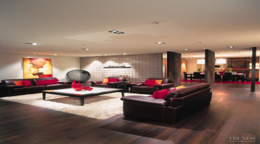 Oversize leather furniture was specified to balance the ceiling, floor, flooring, hardwood, interior design, living room, lobby, room, wood, wood flooring, gray, black