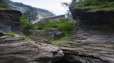 The visitor centre located at the top of cliff, escarpment, geological phenomenon, geology, mountain, mountain range, mountainous landforms, ravine, rock, sky, terrain, tree, water, black, gray