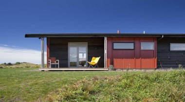 Exterior view of red wall and yellow folding-chair cottage, facade, home, house, property, real estate, shack, shed, sky, blue