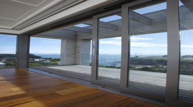 Large sliding doors disappear to reveal breathtaking sea architecture, daylighting, door, home, house, interior design, real estate, structure, window, gray