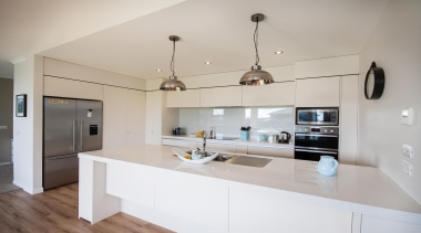 Modern galley kitchen is the heart of the countertop, interior design, kitchen, real estate, gray