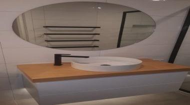 Sleek black tapware with timber top. Note the bathroom, plumbing fixture, sink, tap, toilet, toilet seat, gray