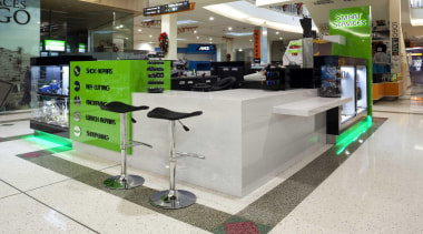 Kiosk designed with matching green neon light - product, retail, gray