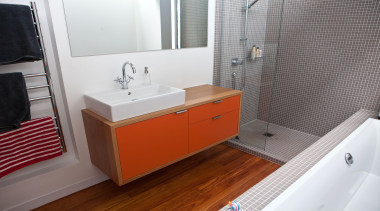 Orange lacquered cabinet fronts bring a punch of bathroom, bathroom accessory, bathroom cabinet, floor, home, room, sink, tile, gray