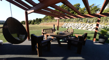 A patio with timber based decor at a furniture, outdoor structure, property, table, black