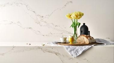 Caesarstone's interpretation of Statuario marble; Statuario Nuvo brings interior design, product design, still life photography, table, vase, yellow, white