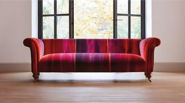 A Harlequin velvet that will make any piece angle, chair, chaise longue, coffee table, couch, floor, flooring, furniture, hardwood, interior design, living room, loveseat, product design, sofa bed, studio couch, table, wood, wood flooring, gray