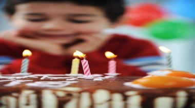 A little boy about to blow out his baked goods, baking, birthday, birthday cake, cake, cake decorating, chocolate cake, dessert, flavor, food, icing, sweetness, torte, red