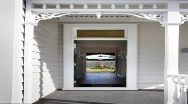 The main entry provides lines of sight through architecture, door, estate, home, house, structure, window, gray, white