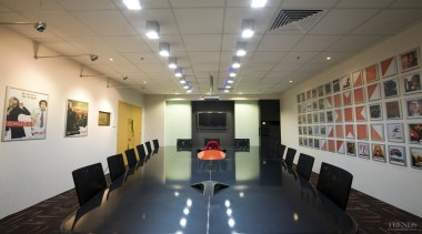 A racing car emerges from the conference table ceiling, conference hall, exhibition, interior design, gray, black