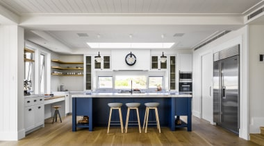 This kitchen serves as the focal point for building, cabinetry, ceiling, countertop, design, dining room, floor, flooring, furniture, hardwood, home, house, interior design, kitchen, laminate flooring, property, room, table, wood flooring, gray