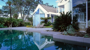 view across pool towards house showing plantings, outdoor arecales, cottage, estate, home, house, palm tree, property, real estate, reflection, resort, sky, swimming pool, villa, water, teal