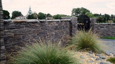 Interlocking stone wall with black iron gate, with grass, grass family, landscape, landscaping, outdoor structure, plant, walkway, wall, white