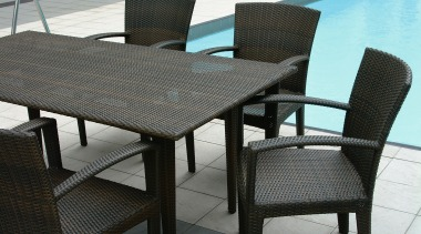 Dedon outdoor dining suite next to pool. - chair, furniture, outdoor furniture, outdoor table, product design, table, wicker, black, gray