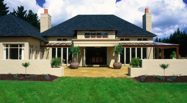 A view of the exterior of a home cottage, estate, facade, farmhouse, grass, home, house, landscape, landscaping, lawn, mansion, property, real estate, residential area, roof, siding, sky, window, yard, green