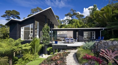 Exterior view of a 1970s felling Nz House architecture, cottage, elevation, estate, home, house, landscape, neighbourhood, plant, property, real estate, residential area, roof, tree, villa, yard, black