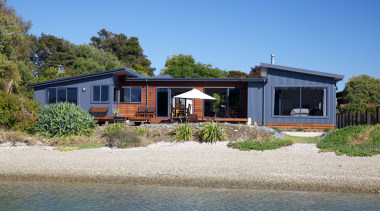 Nestled among the trees on the shoreline at cottage, estate, facade, home, house, property, real estate, sky, villa, water, teal