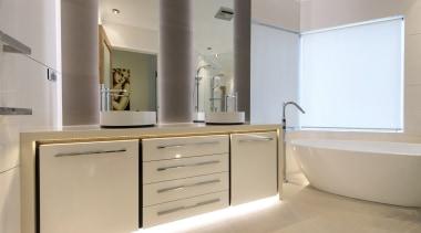 In-cabinet, under counter lighting adds definition to this bathroom, bathroom accessory, bathroom cabinet, cabinetry, countertop, floor, interior design, room, sink, gray
