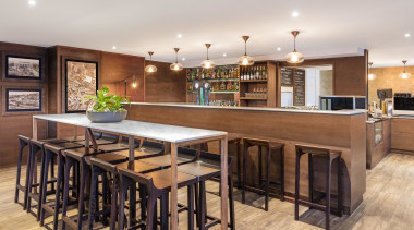 A warm, inviting bar and restaurant greets guests countertop, flooring, interior design, kitchen, real estate, table, white