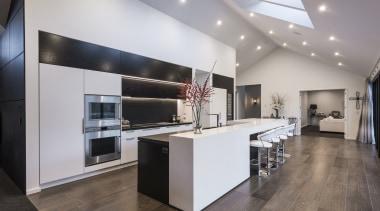 A stepped countertop helps evoke the spatial features countertop, floor, flooring, interior design, kitchen, gray