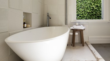 A nib wall separates the bathing zone from bathroom, bathroom sink, bathtub, ceramic, floor, interior design, plumbing fixture, product design, tap, tile, toilet seat, gray