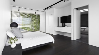 The monochromatic colour palette continues in this master bed, bed frame, bedroom, floor, flooring, furniture, interior design, room, white, black