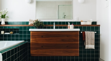 Evergreen tiles and a walnut-clad cantilevered vanity make