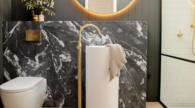A freestanding vanity basin is backed by a