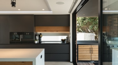 A fixed low glass window is incorporated into architecture, cabinetry, countertop, house, interior design, kitchen, black, gray