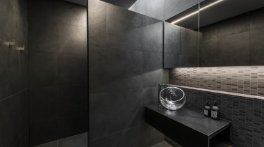 Designer Davinia Sutton created a moody space with architecture, bathroom, building, floor, flooring, house, interior design, material property, plumbing fixture, property, room, tile, wall, black