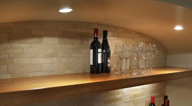 Because of its expansive and wide-open layout, a countertop, floor, flooring, glass, interior design, liquor store, table, tile, wall, wine cellar, winery, brown