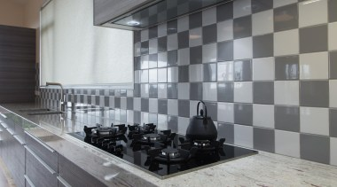 Lustrous stove top contrasts with glossy tile feature.For countertop, floor, flooring, interior design, tile, wall, gray