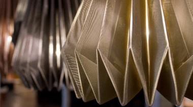 A range of folded metallic fabrics  are interior design, lampshade, light, light fixture, lighting, lighting accessory, material, brown, black