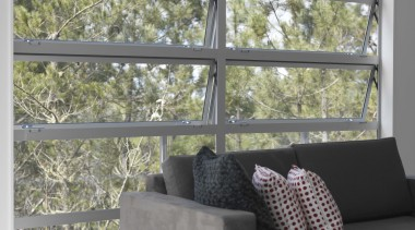 Awning windows symmetrically frame the outdoor treescape. chair, couch, daylighting, furniture, home, house, interior design, living room, loveseat, sofa bed, wall, window, window covering, window treatment, gray