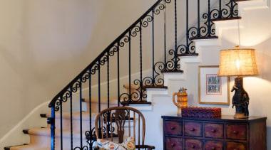The Foyer had the original iron railing. The floor, flooring, handrail, home, interior design, stairs, wall, wood, gray