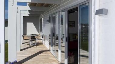 View of white exterior and wooden deck - door, floor, window, gray, white