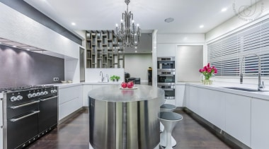 A curved island encourages better flow through this countertop, cuisine classique, interior design, kitchen, real estate, room, gray