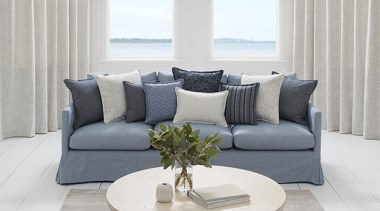 Offering a calm coastal aesthetic and soft tactile angle, coffee table, couch, floor, furniture, home, interior design, living room, loveseat, sofa bed, table, window, window covering, window treatment, gray