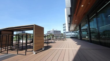 This large beautiful staff decking facility was build architecture, boardwalk, deck, house, mixed use, real estate, sky, walkway, wood, black, teal