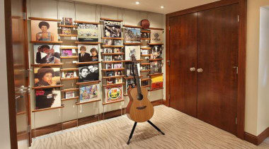 Because of its expansive and wide-open layout, a bookcase, cabinetry, closet, floor, flooring, furniture, hardwood, interior design, room, shelving, brown, orange