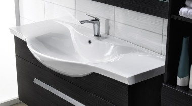 A classic style is formed when sweeping edges angle, bathroom, bathroom accessory, bathroom cabinet, bathroom sink, plumbing fixture, product, product design, sink, tap, white, black