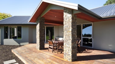 Covered outdoor living area with schist pillarsBuilt by facade, home, house, outdoor structure, property, real estate, siding