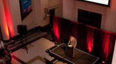 Melle de Pater addresses the crowd - At auditorium, red, brown, black